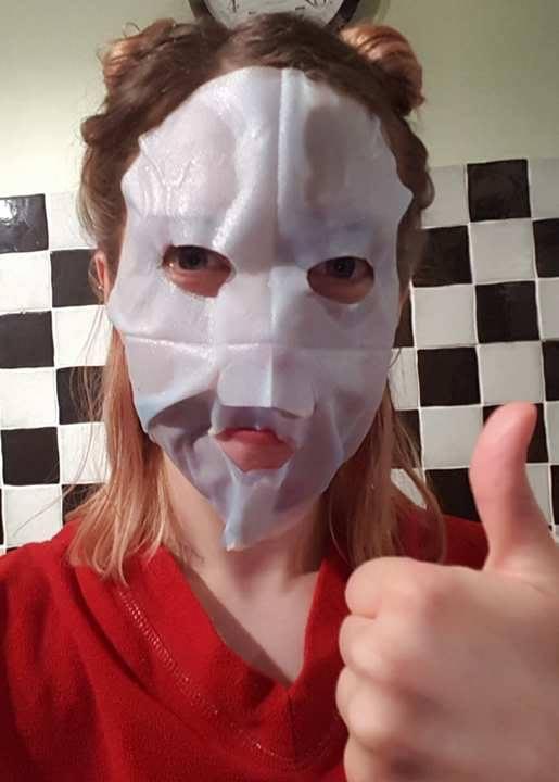 Putting on the Garnier Moisture Bomb Sheet Mask