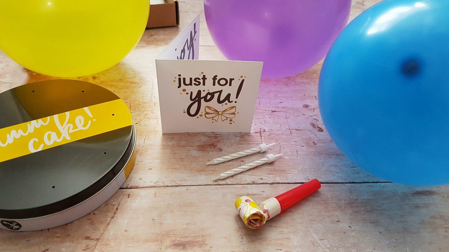 Balloons, card and candles with Bakerdays letterbox cake