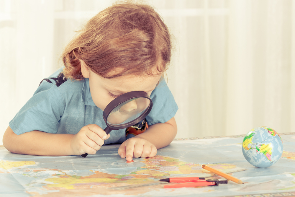 Child looking at map through a magnifying glass