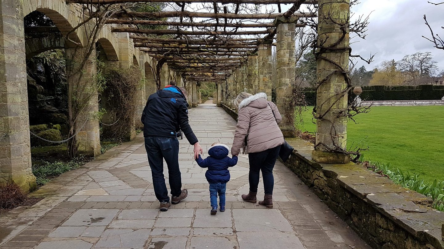 Toddler holding grandparents hands in the Italian garden at Hever Castle