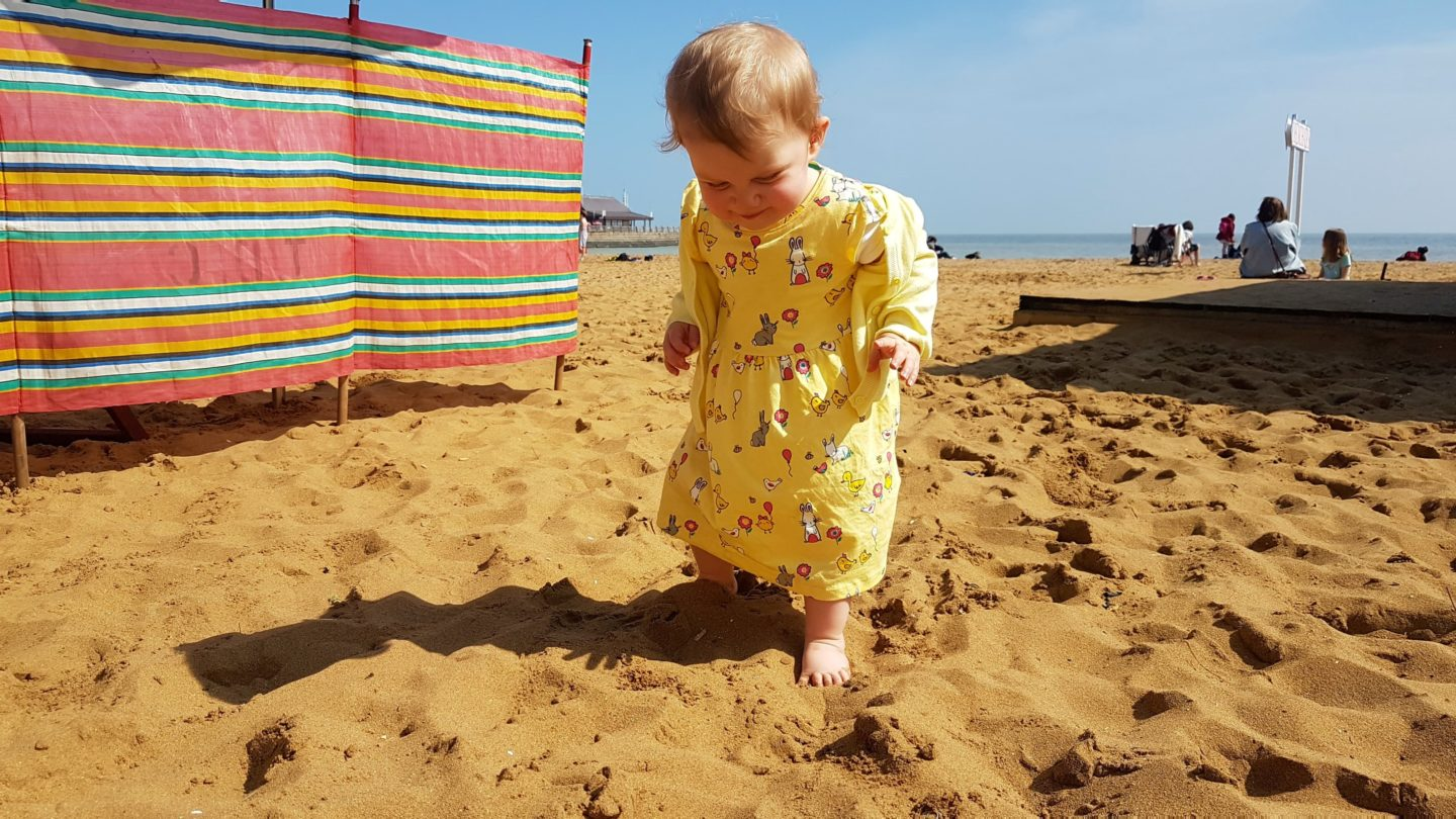 Toddler feeling sand on toes