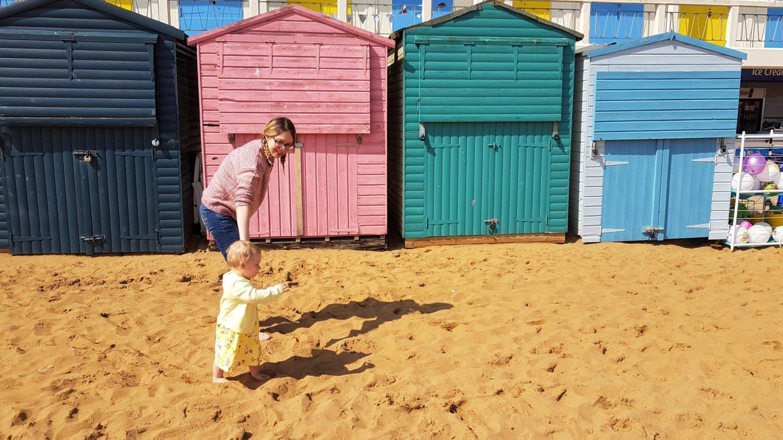 Mum and baby walking past beach huts