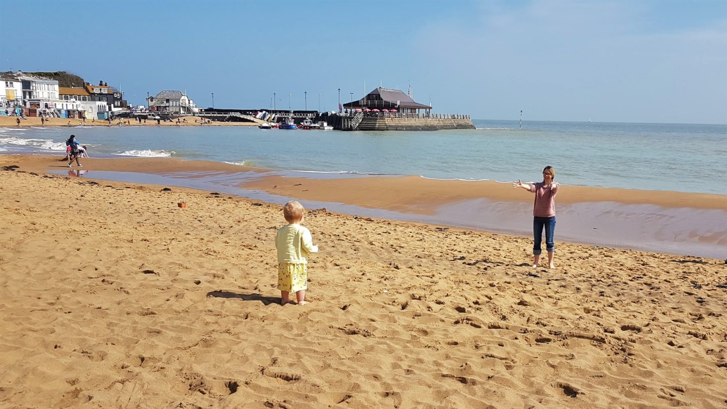 Mum holding out arms to baby on the beach