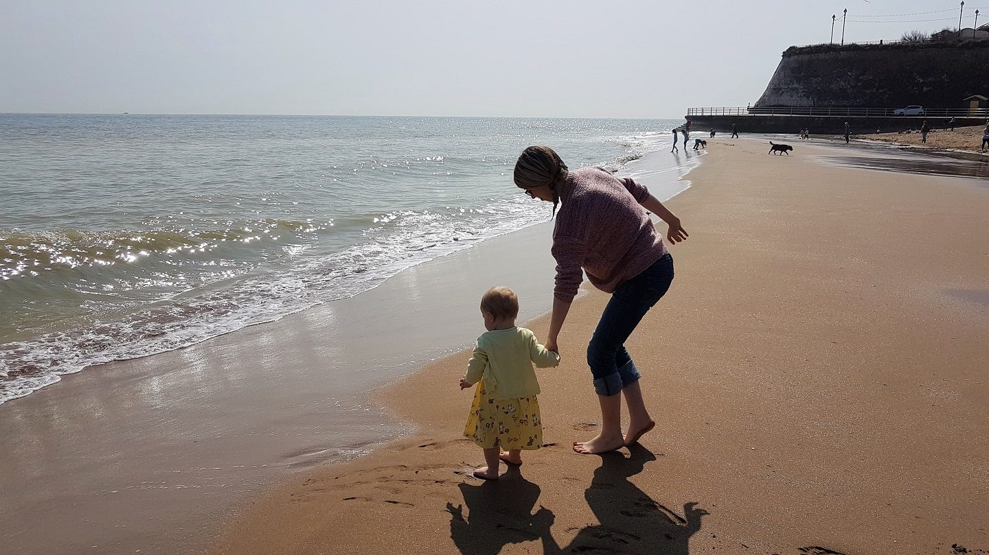 Mum and baby standing by the sea