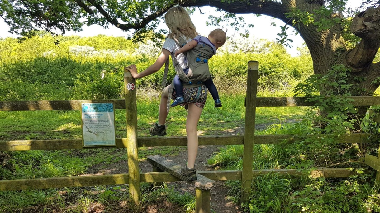 Baby wearing over a turnstile on a country walk