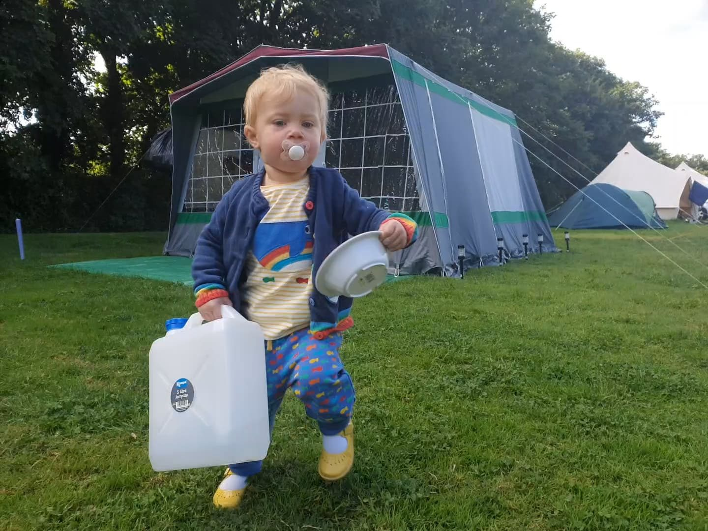 Frugi wearing toddler camping in a tent in Cornwall