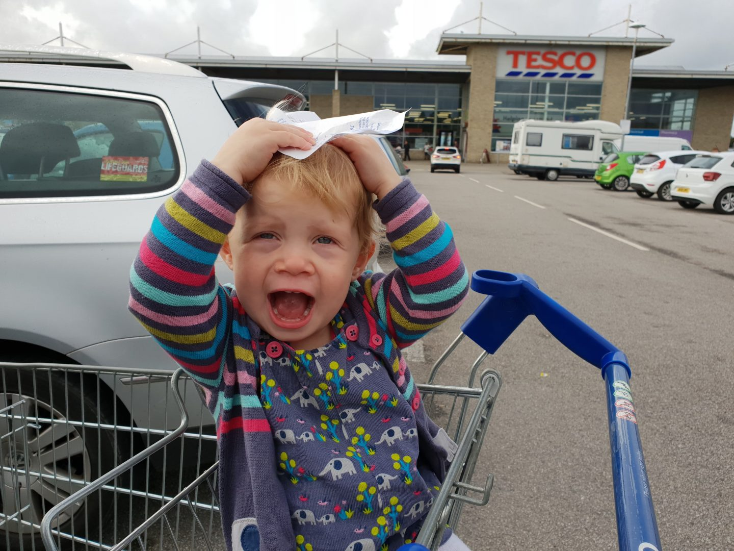 Toddler with receipt outside Tesco Helston