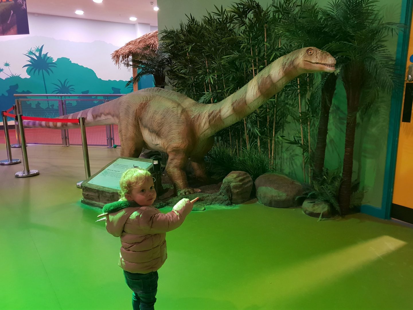 Toddler with animatronic dinosaur at Dinotropolis, Bluewater