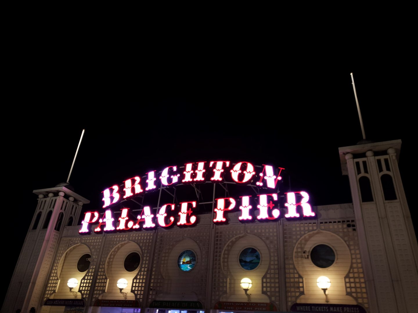 Brighton Palace Pier sign lit up in red and white candy stripes for Christmas
