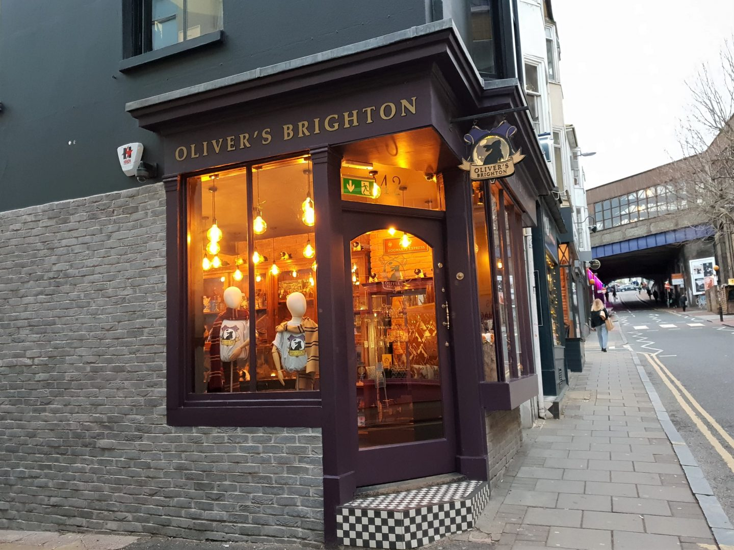 Oliver's Harry Potter shop front in Brighton - purple paint with old fashioned sign writing, a checkered step and inviting warm lights within