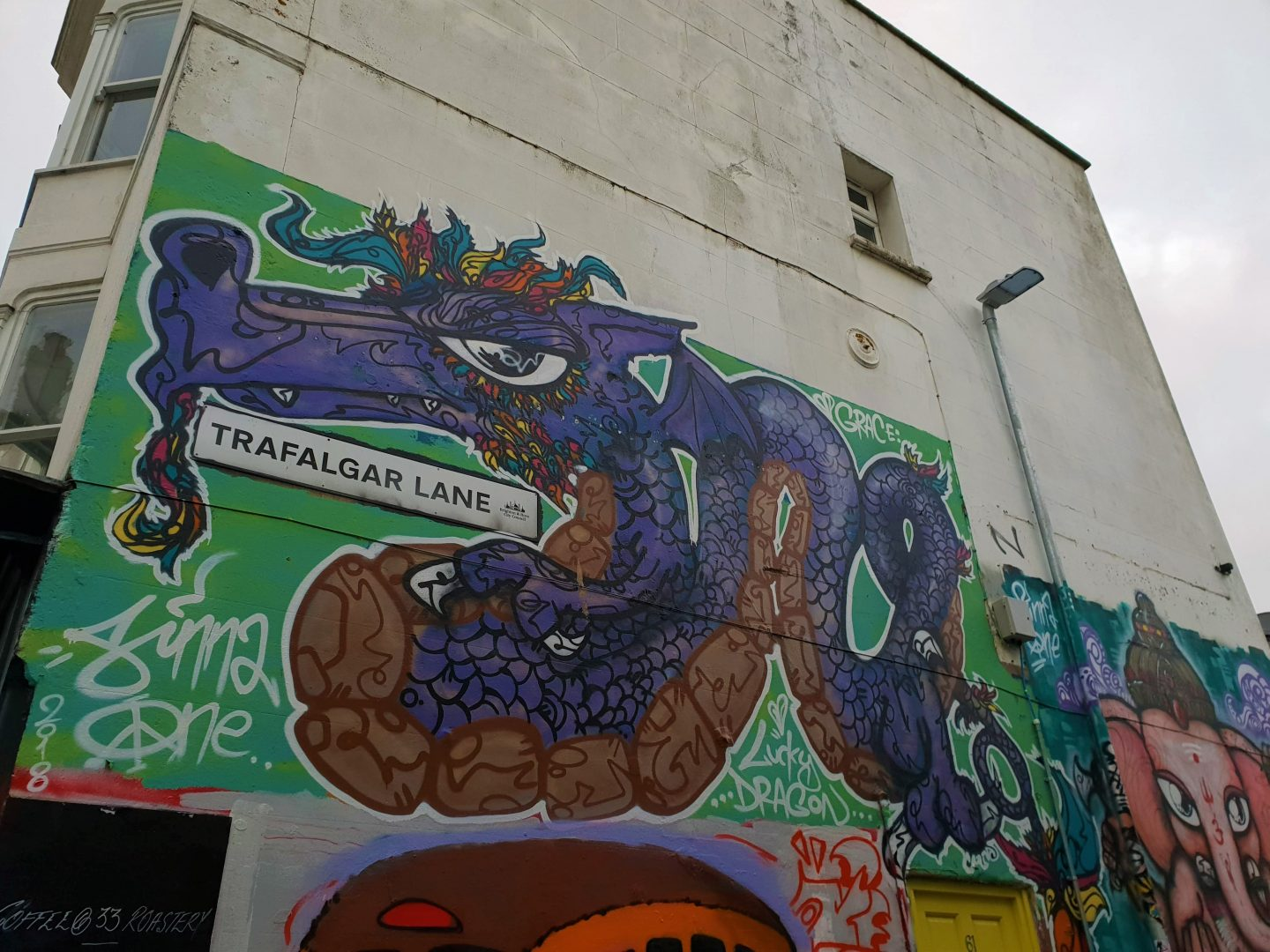 Graffiti artwork of a large purple and orange dragon on a green background around the sign for Trafalgar Lane Brighton