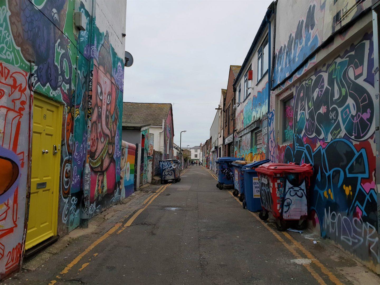 Graffiti street art on walls and wheelie bins in Trafalgar Lane Brighton
