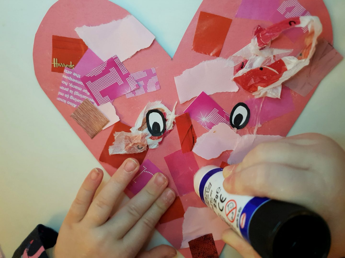 Toddler gluing face onto Valentine's heart craft