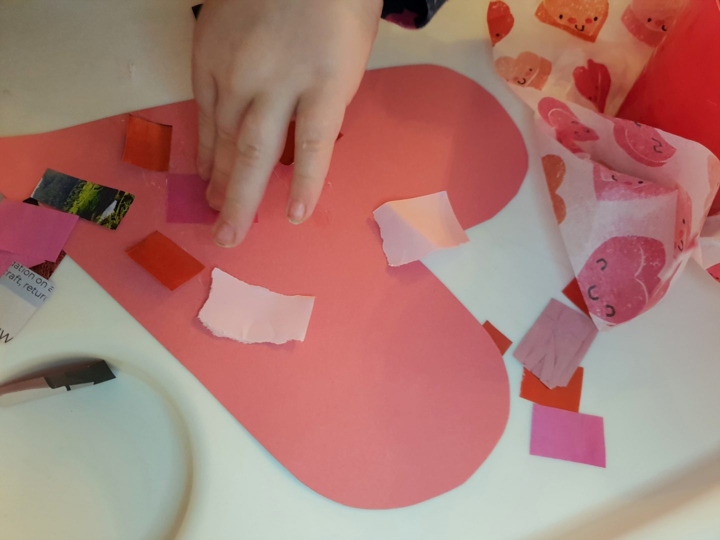 Sticking scrap paper to heart, Valentine's Day craft