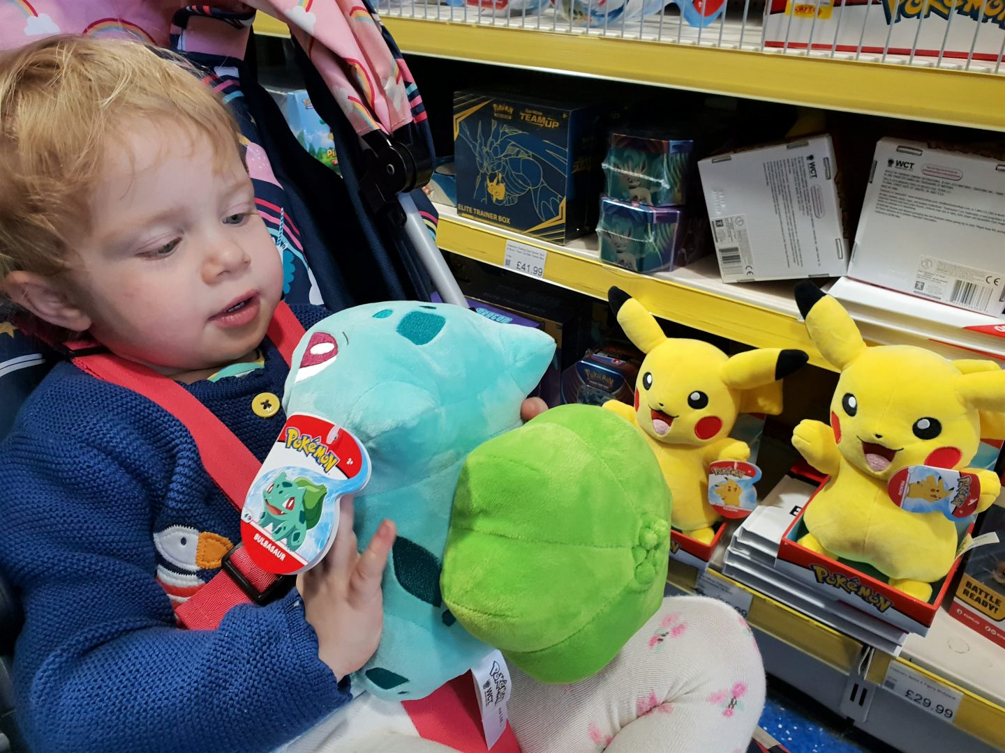 Toddler choosing Bulbasaur Pokemon toy at Smyths Toys, South Aylesford Retail Park as Pikachu looks on