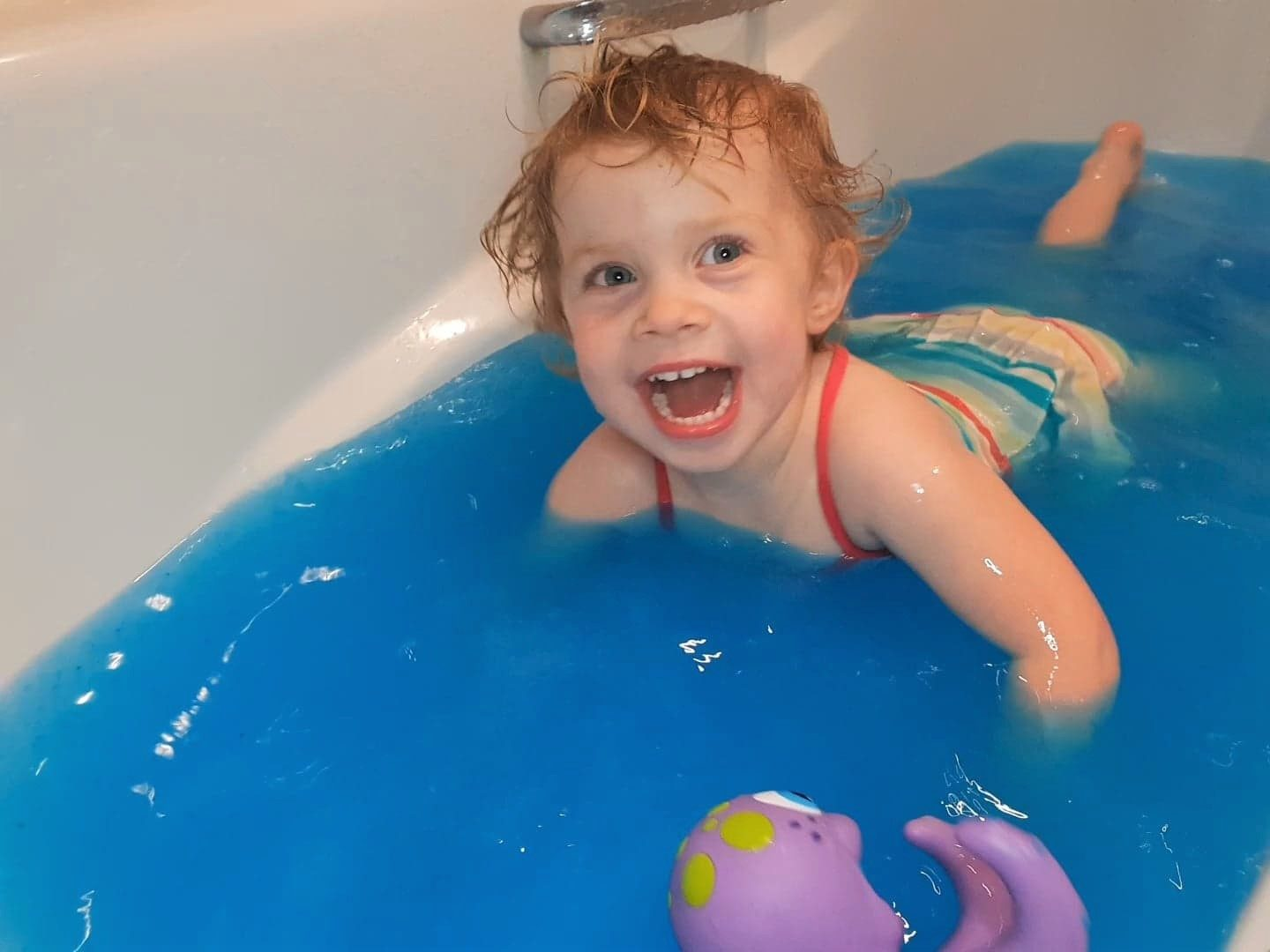 Toddler swimming in Blue Goo slime baff