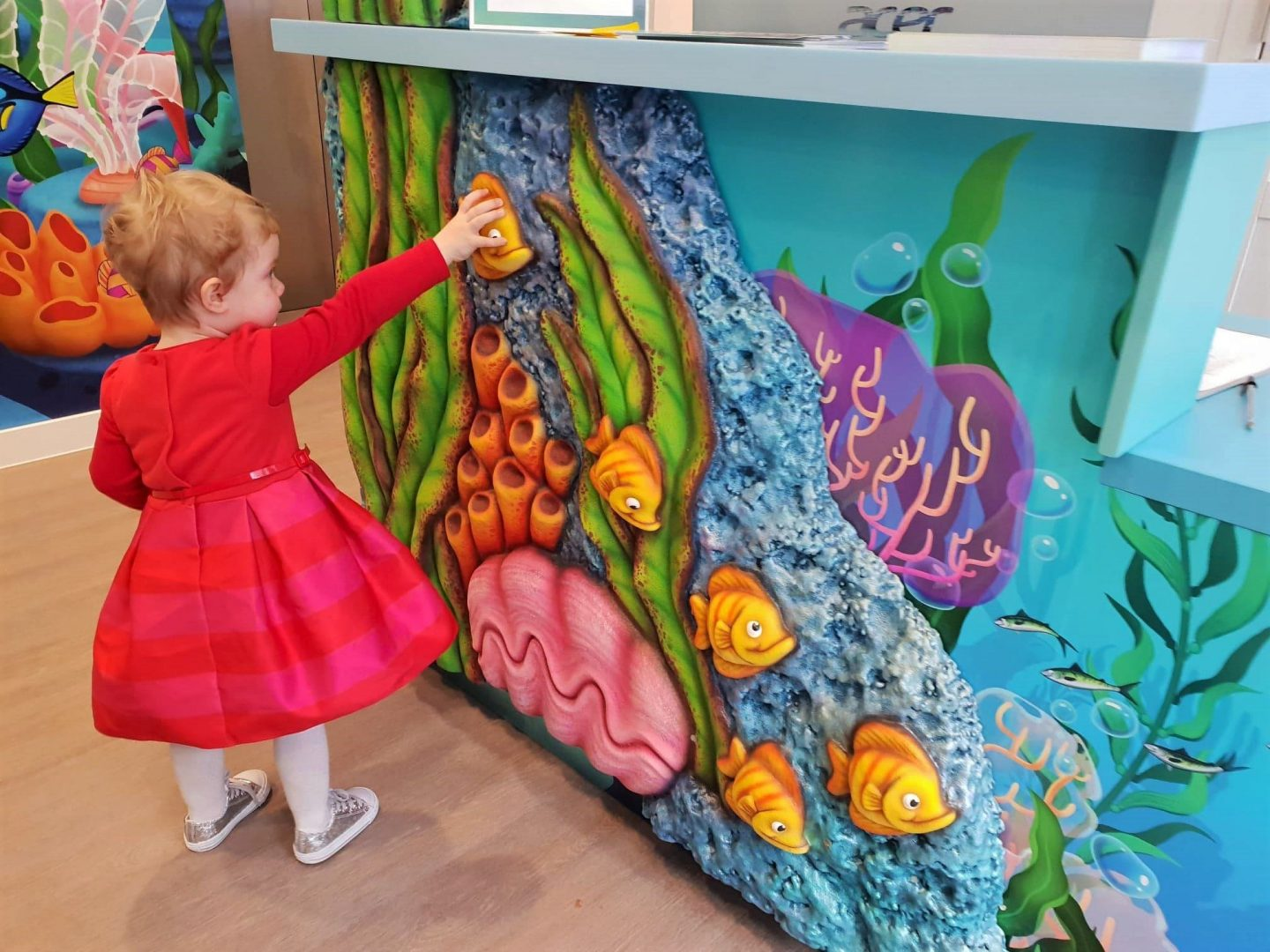 Toddler touching fish on Happy Kids Dental reception desk in Chelsea