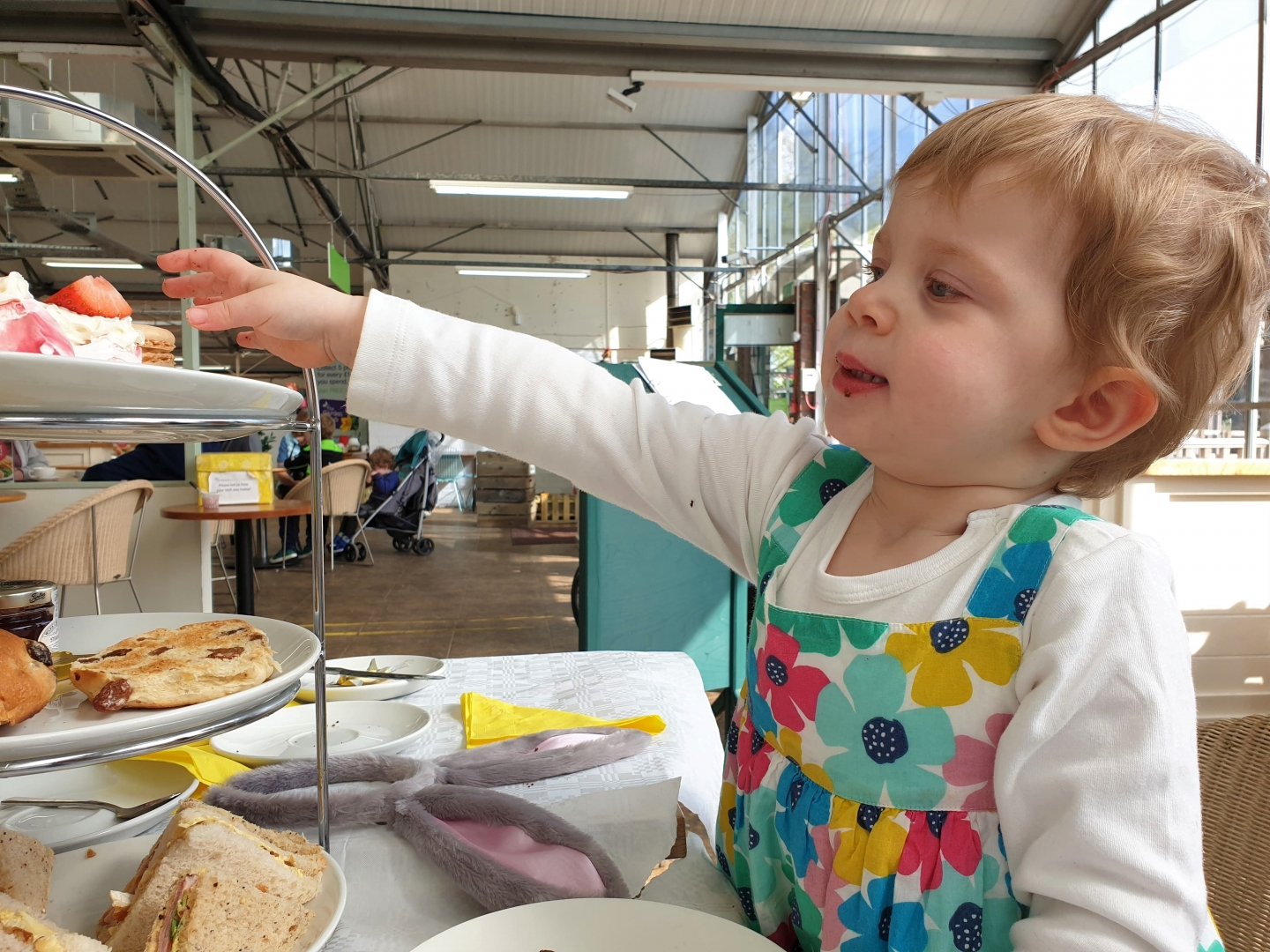 Toddler reaching for cake on top of Easter afternoon tea stand