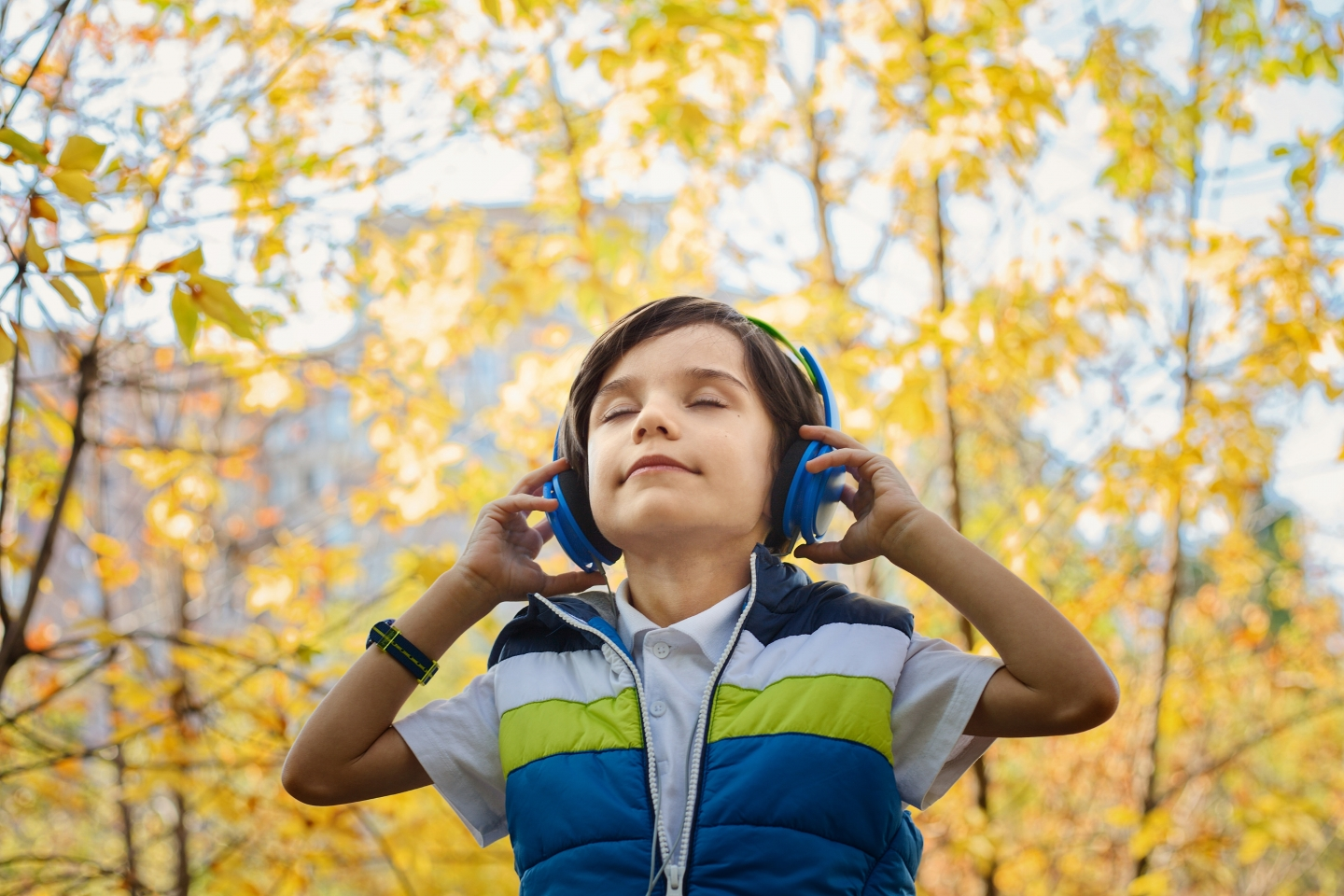 Child listening to headphones in nature