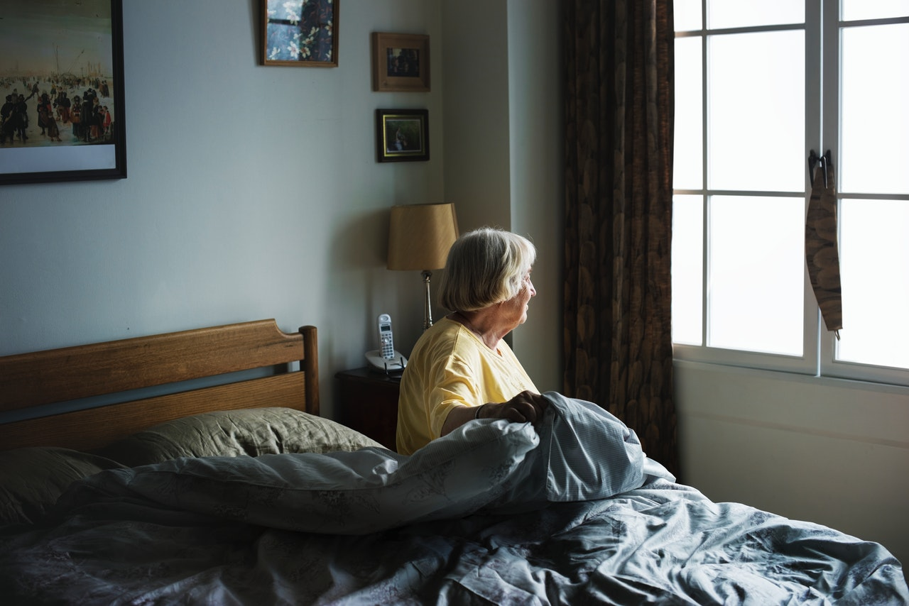 Old woman on bed in care home
