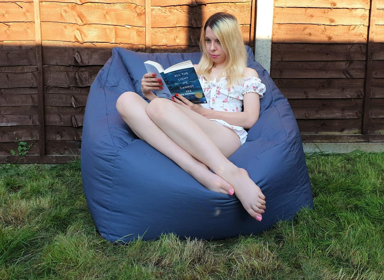 Sitting on Icon outdoor bean bag reading a book