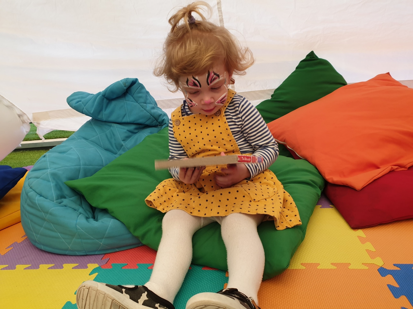Toddler reading with face paint on
