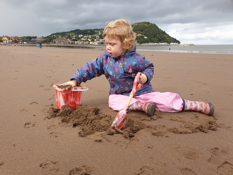 Toddler making sandcastles on beach