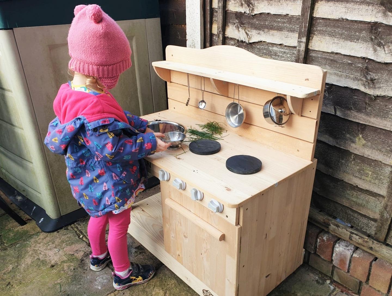 Preschooler playing with mud kitchen
