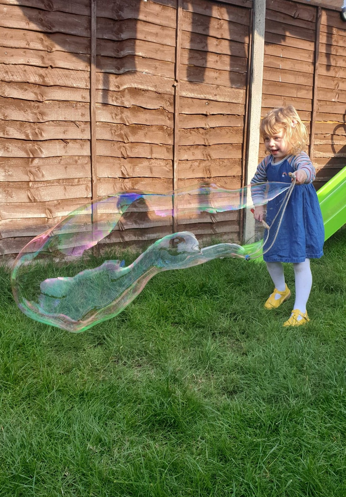 Toddler blowing Dr Zigs giant bubbles in garden
