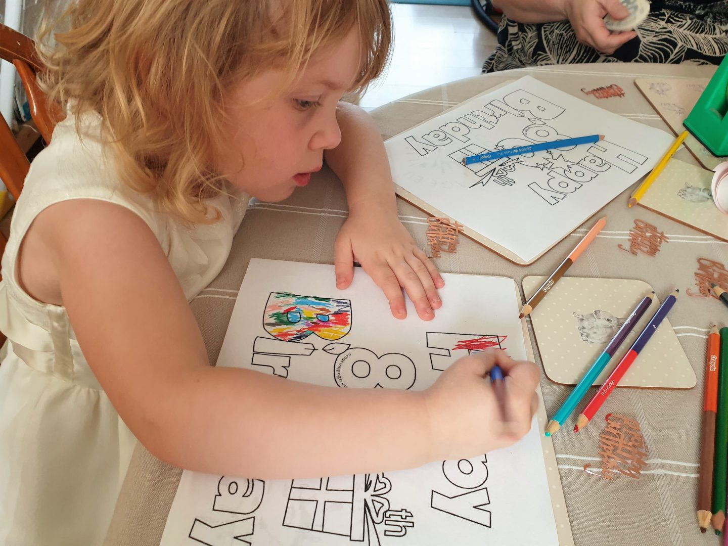 Child colouring in birthday banner