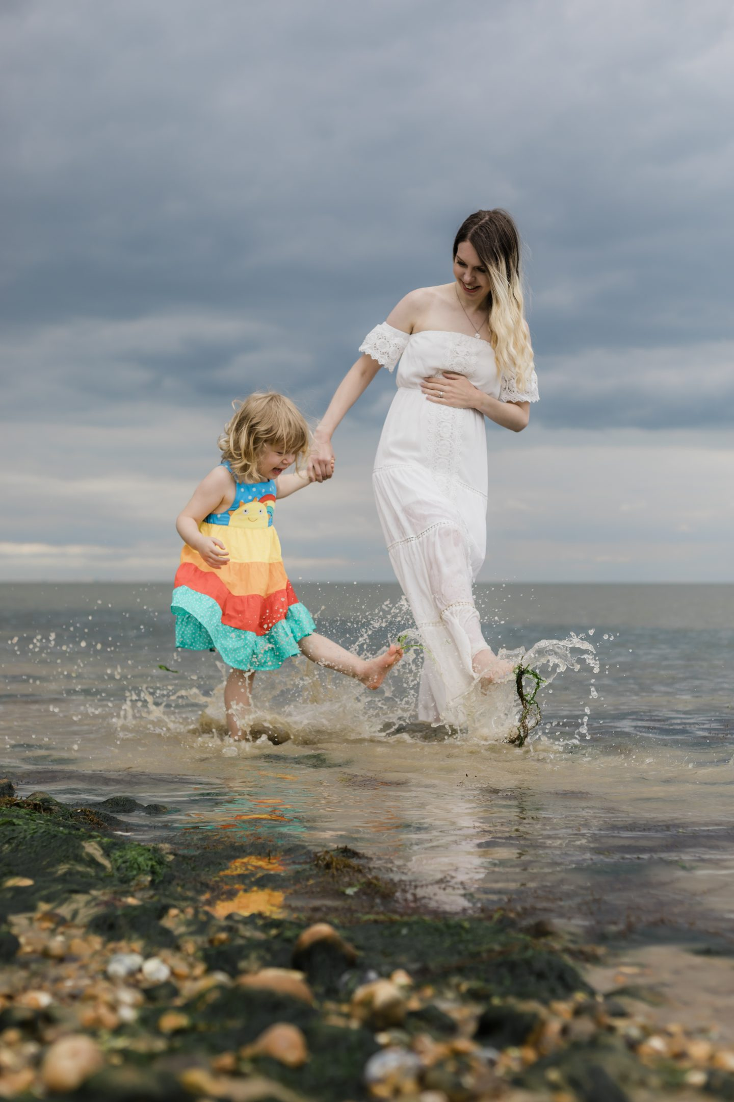 Mum splashing in sea with child