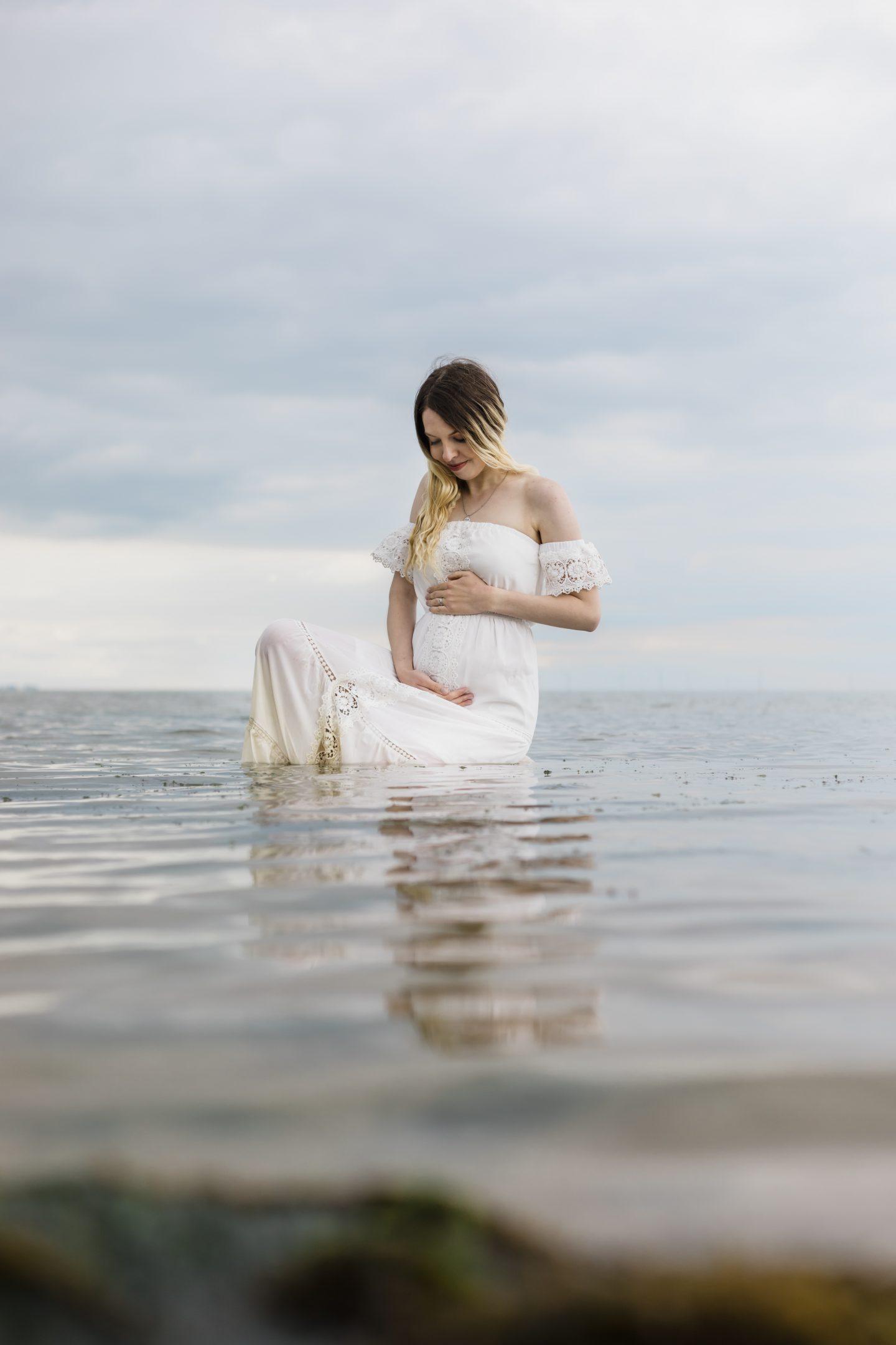 Cradling baby bump in the sea