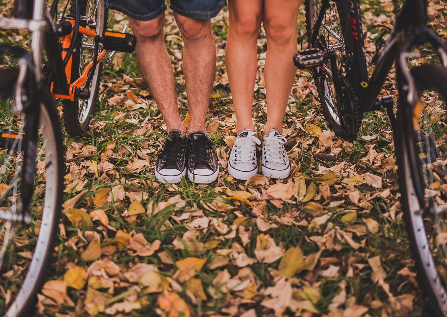Two people with bicycles stood on fallen leaves